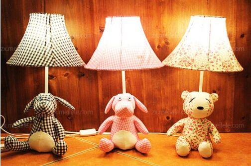 布艺台灯灯罩做法 1 :方形灯罩 做方形的布艺台灯灯罩是最简单的,如果对手工不太自信,那么推荐选择这种形状的灯罩。有些朋友担心方形灯罩效果不好,不能营造温馨的感觉。其实这种形状非常优雅,像古代的宫灯,小编建议大家用比较轻薄透明的素色布料来制作,再用颜料淡淡勾勒几笔水墨,或者写两行字,浓浓的古风意境就被营造出来了,艺术美感非常浓厚。 1.